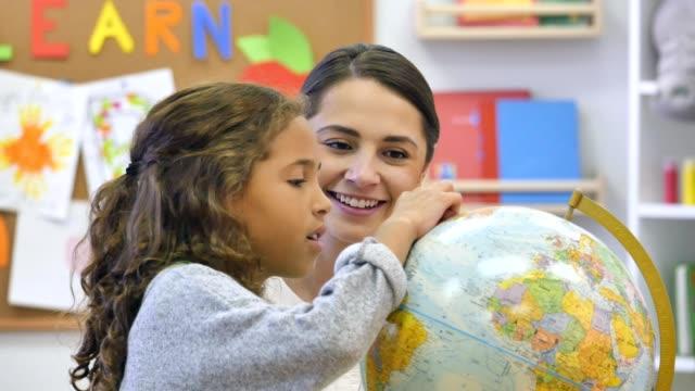 curiosa studentessa elementare studia globo - geografia fisica video stock e b–roll