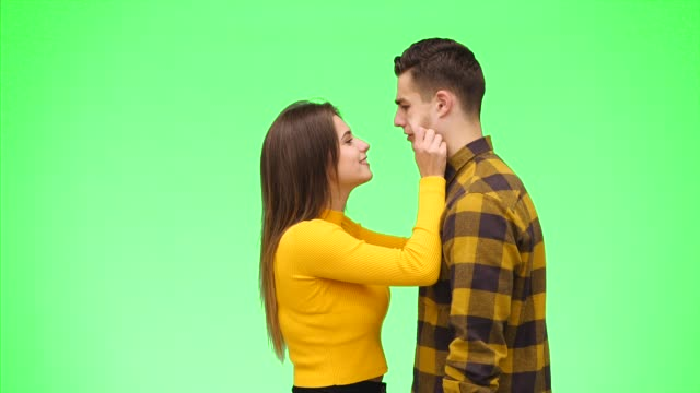 Curious girl is pulling her boyfrind's cheeks and ears on a green background. Their noses are rubbing. Close up. Copy space. 4K.