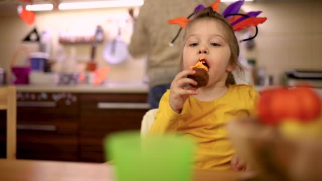 vídeos y material grabado en eventos de stock de chica curiosa lamiendo la guinda de la magdalena de halloween y ella simplemente disfrutar de ella - halloween covid
