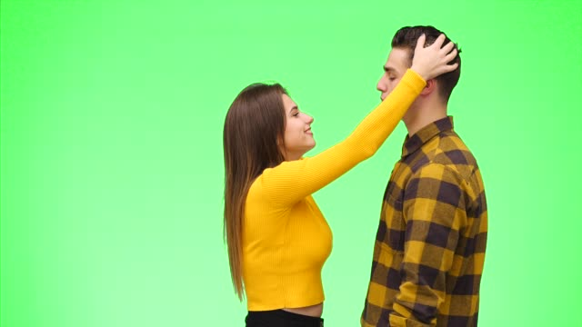 Curious girl pats her boyfrind's hair and is pulling him closer to kiss, on a green background. Close up. Copy space. 4K.
