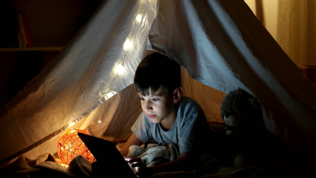 Curious kid boy secretly watching forbidden censored content on Tablet