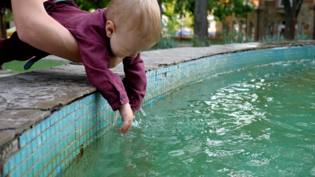 curious kid trying to touch fountain water at nature video