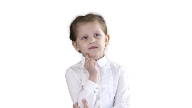 A curious little girl stands and thinks on white background