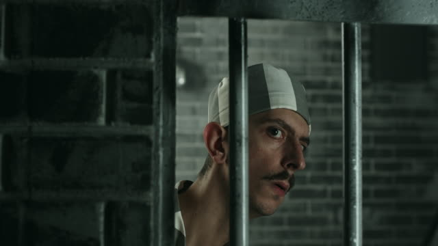 Curious men looking through the prison bars video