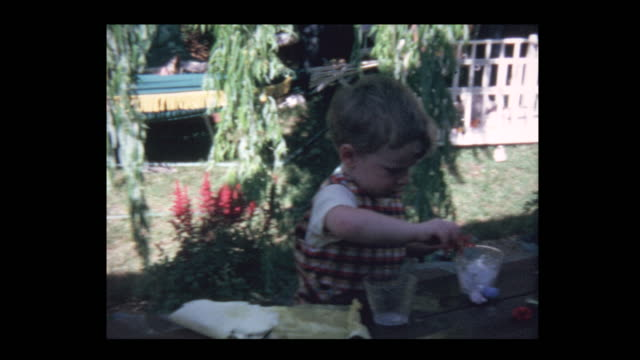 1971 curious toddler boy plays with ice cubes at windy picnic table - hotel reception filmów i materiałów b-roll