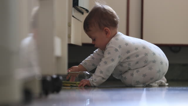 curious toddler exploring kitchen cupboards opening and discovering cabinets dropping object - pojęcia i zagadnienia filmów i materiałów b-roll