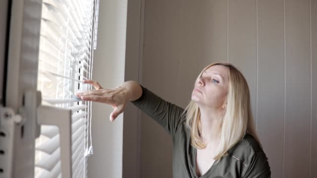 Curious young woman spying, peeking through the blinds in her home