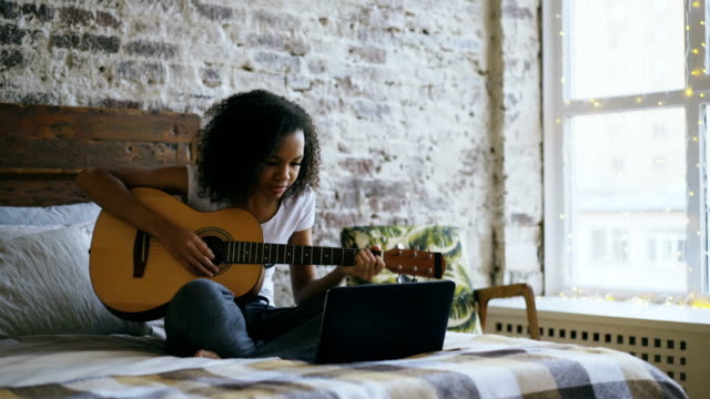 vídeos de stock e filmes b-roll de curly african american teenager girl concentraing learning to play guitar using laptop computer sitting on bed at home - instrumental