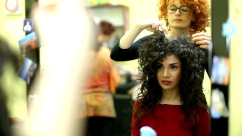 vidéos et rushes de jeune fille brune frisée, venir sa nouvelle coiffure coiffeur - coiffure