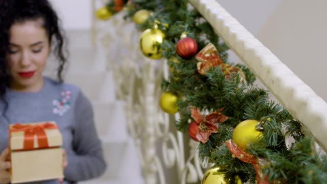 stockvideo's en b-roll-footage met curly brunette geeft een gift van kerstmis camera - christmas tree
