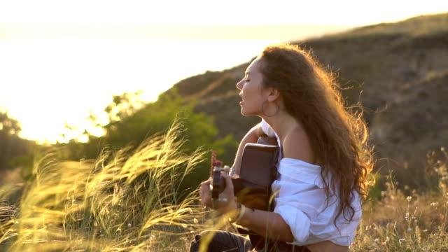 カーリーのジプシー ブルネットの少女ギターを演奏し、歌う湾の斜面において - 田舎のライフスタイル点の映像素材/bロール