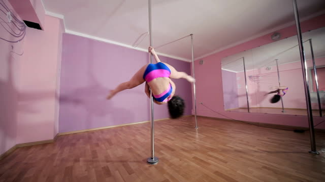 Curly girl with sexy body doing a tricks on the pole video
