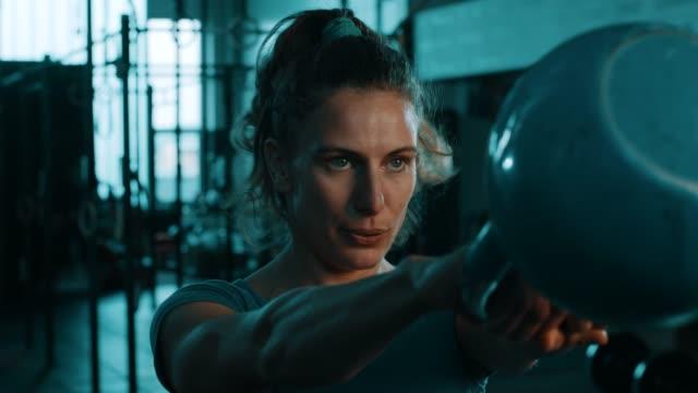 vídeos de stock, filmes e b-roll de mulheres de cabelos cacheados, fazendo exercícios com kettlebell no ginásio - pesado peso