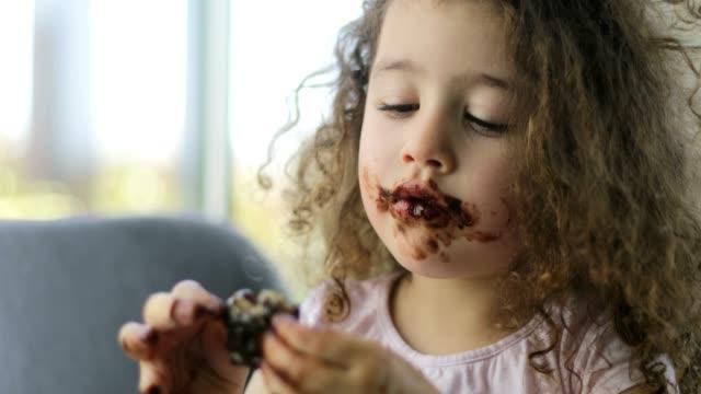 vídeos de stock, filmes e b-roll de mãe jovem de cabelos encaracolados e filha de cabelos encaracolados estão fazendo bolachas caseiras em casa. eles usam chocolate de mel e manteiga de amendoim. a garotinha aprende a cozinhar com a mãe. eles estão se divertindo juntos durante os dias de - chocolate