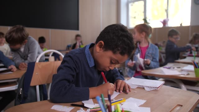 Curly mixed race schoolboy drawing in classroom Cute preadolescent schoolboy drawing with concentration during art lesson in elementary school. Focused mixed race primary school student enthusiastically creating picture in drawing lesson primary school stock videos & royalty-free footage