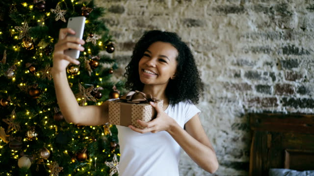 Curly teenage girl chatting online conversation using smartphone camera at home near Christmas tree video