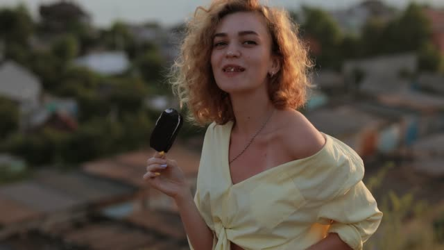 Curly woman eating ice cream above the city