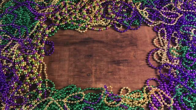 curtain of Mardi Gras beads parting to reveal colorful bead border