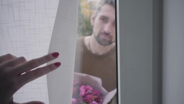 Curtain opening on the glass door and adult Caucasian gray-haired man standing behind it with a bouquet of violet roses asking to open and smiling. Young female hand clothing the curtain at the end. Curtain opening on the glass door and adult Caucasian gray-haired man standing behind it with a bouquet of violet roses asking to open and smiling. Young female hand clothing the curtain at the end. relationship breakup stock videos & royalty-free footage