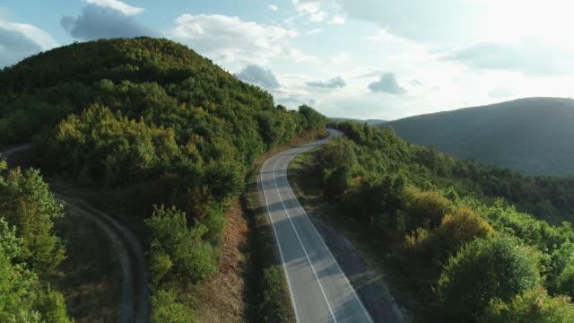 curva strada di montagna dal drone - strada tortuosa video stock e b–roll