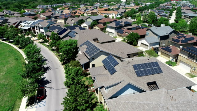 vídeos de stock e filmes b-roll de curved layout mueller new development suburb with rooftop solar panels in austin , texas - close to far backing away from solar rooftops on houses - energia solar