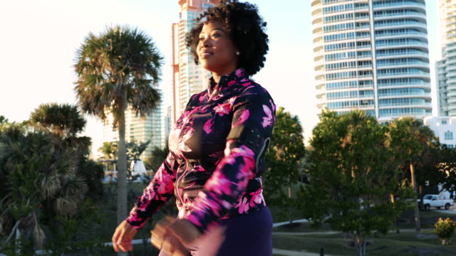 curvy young black woman relaxation exercise and stretching in miami beach public park - sovrappeso video stock e b–roll