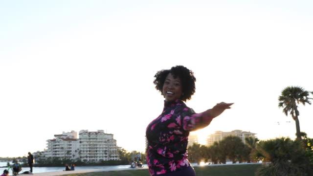 kurvige junge schwarze frau entspannungsübung und stretching in miami beach öffentlichen park - übergrößen model stock-videos und b-roll-filmmaterial
