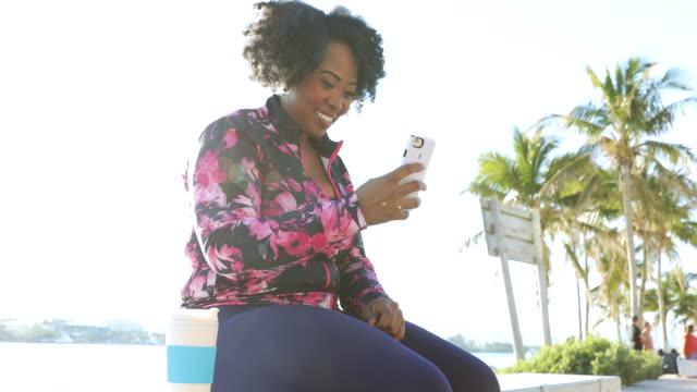 düzgün vücutlu genç siyah kadın egzersiz oturum cep telefonunuzda sohbet bir mola - orta yetişkin stok videoları ve detay görüntü çekimi