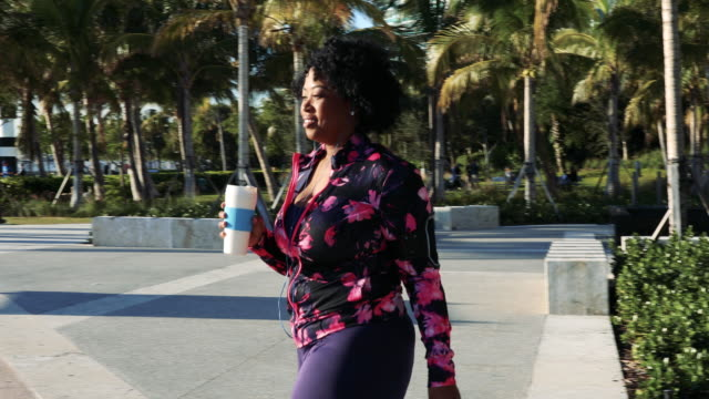 curvy young black woman walking, jogging and running in miami beach public park - body positive video stock e b–roll