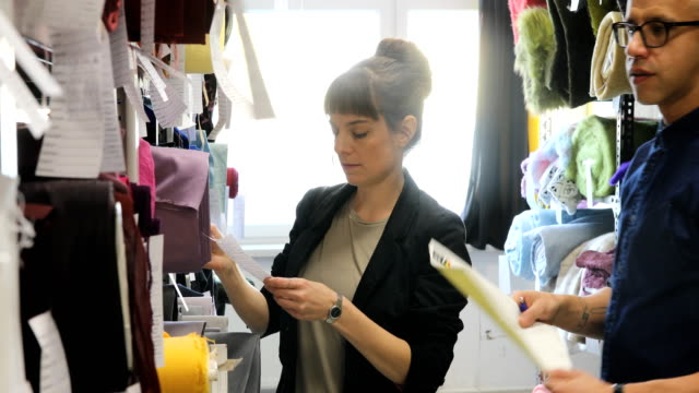 customer and manager examining fabrics in rack - индустрия моды стоковые видео и кадры b-roll