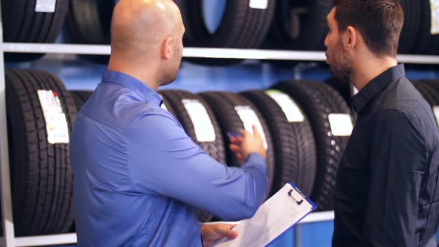 customer and salesman at car service or auto store business, maintenance and people concept - male customer and salesman with clipboard showing wheel tires at car repair service or auto store tires stock videos & royalty-free footage