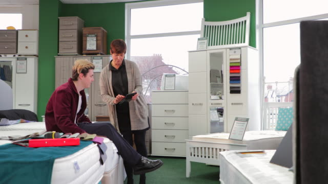 Customer Assistance in Furniture Shop Young man is getting advice from a sales clerk in a furniture shop. He is trying a new mattress. furniture stock videos & royalty-free footage