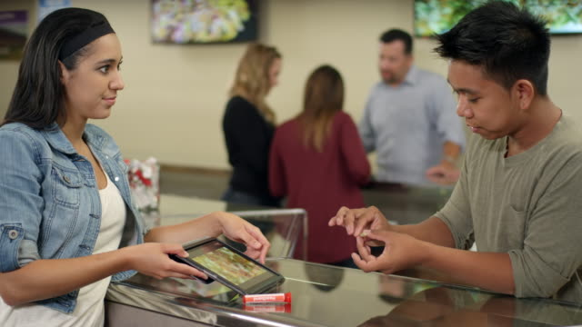 Customer at marijuana shop weighs joint in hand and looks at product on tablet video