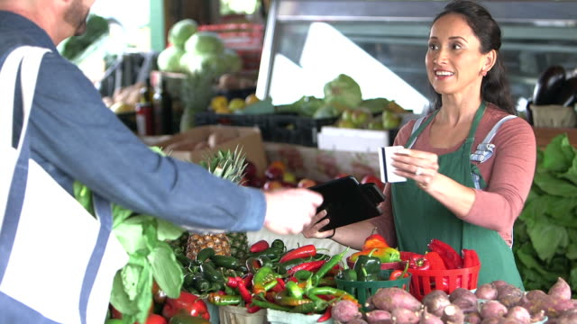 Customer at produce stand paying with credit card A customer making a purchase at a produce stand pays with a credit card. The Hispanic worker swipes the card through a reader attached to a digital tablet. credit card purchase stock videos & royalty-free footage