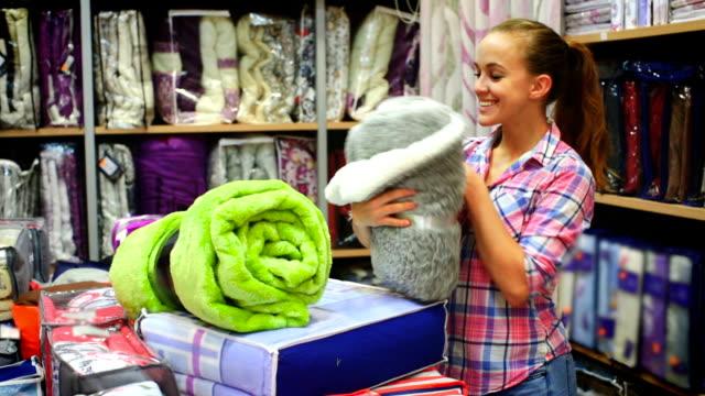 customer boasting of her new blanket Girl customer boasting of her new blanket and coverlet in textile shop blanket stock videos & royalty-free footage