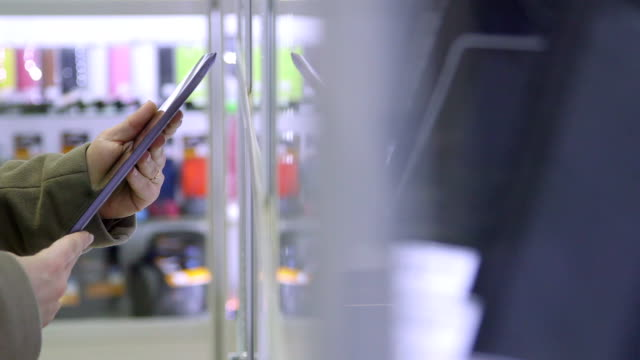 Customer buying digital tablet in electronics store
