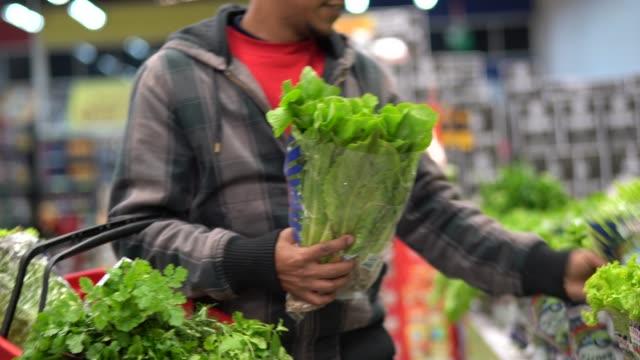 customer buying greens on supermarket - lattuga video stock e b–roll