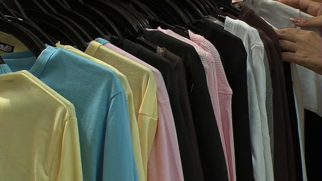 il cliente sceglie t-shirt in abiti negozio - modella negozio video stock e b–roll