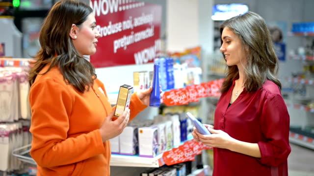 kunde sie kosmetikprodukte im supermarkt - kosmetik beratung stock-videos und b-roll-filmmaterial