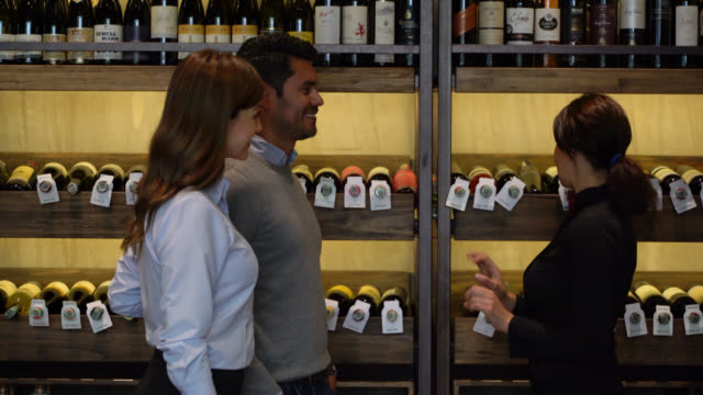 Customer couple asking for a wine suggestion to female sommelier at a wine cellar who helps them very cheerfully