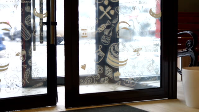 Customer entering store on a snowy winter day, holiday shopping
