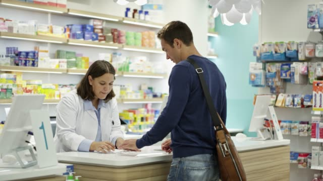 Customer giving prescription to chemist at store Slow motion shot of customer giving prescription to female chemist. Pharmacist checking computer at checkout counter. They are standing at pharmacy. pharmacien stock videos & royalty-free footage