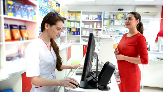Customer in a drugstore searching for medical products Young female pharmacist showing medical products to a female customer in a drugstore pharmacy stock videos & royalty-free footage