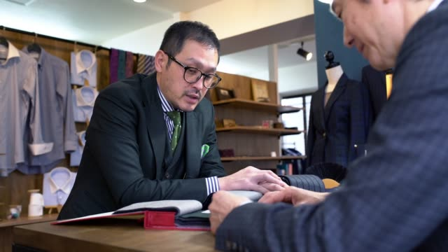 customer looking at fabric swatches with a tailor - tailor working video stock e b–roll