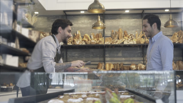 Customer looking at options in the bakery and salesman serving video