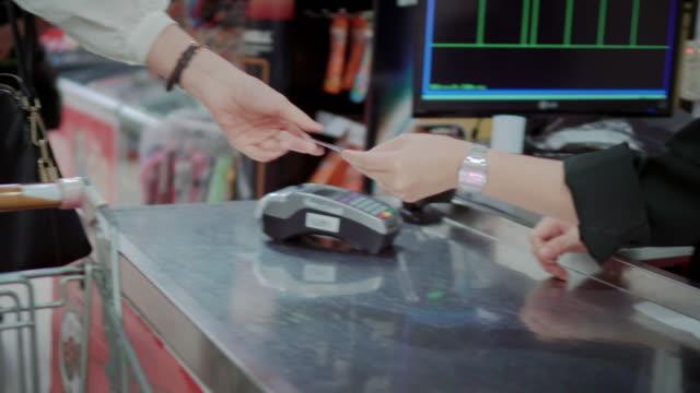 kunden gör contactless betalning med kreditkort i mataffär kassan - spendera pengar bildbanksvideor och videomaterial från bakom kulisserna