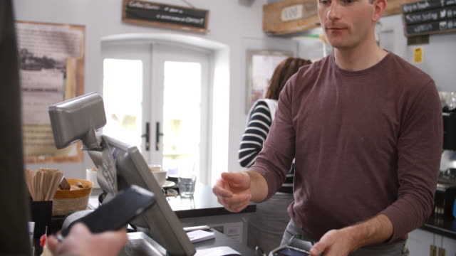 Customer making contactless payment with phone over counter video