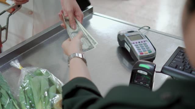 kunden betalar för shopping i mataffär kassan, över axel sköt - spendera pengar bildbanksvideor och videomaterial från bakom kulisserna