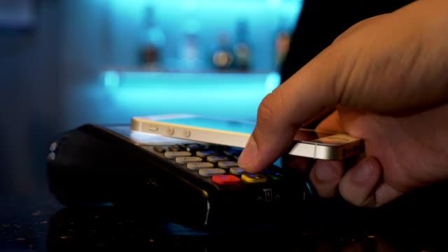cliente che paga con smartphone al pub del ristorante utilizzando pos e tecnologia wireless contactless - conto corrente video stock e b–roll