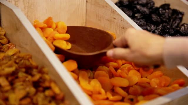 клиент приобретает сухое apricots in grocery - абрикос стоковые видео и кадры b-roll